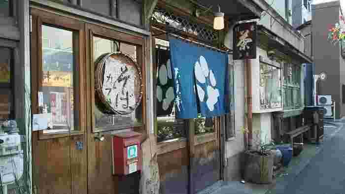 押上駅から十間橋通りを10分ほど歩いたところにある「長屋茶房 天真庵(ながやさぼう てんしんあん)」は、築60年以上の長屋をリノベーションしたカフェです。昭和レトロな木の引き戸に、紺地ののれんが目をひきます。