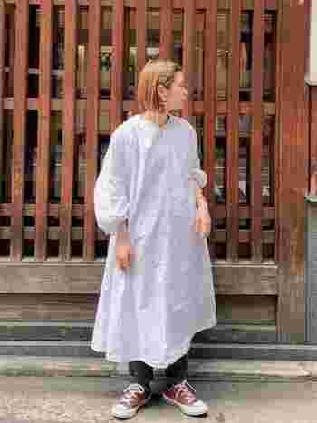 こちらも白ワンピースをレイヤードしたスタイルですが、合わせるアイテムですこしカジュアルな着こなしになっています。バルーン袖のシンプルなコーデにワンポイントのデザインがおしゃれを引き立てます。差し色のスニーカーもGOOD。