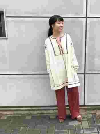お尻まですっぽり隠れる丈の刺繍トップスには、刺繍にも使われている赤色のパンツを合わせて統一感をプラス。刺繍トップスがふわっとしたシルエットなので、ヘアはまとめてすっきりと。