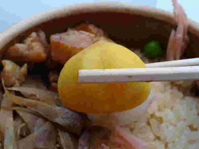 【『峠の釜めし』は、当地ならではの山の幸を用いた、素朴な味わいが魅力のロングセラー弁当。うずらの卵、ささがきごぼう、杏子、椎茸、鶏肉、筍、栗と、発売当初から変わらない具材が、今も炊き込みご飯の上に彩り良く並んでいる。】