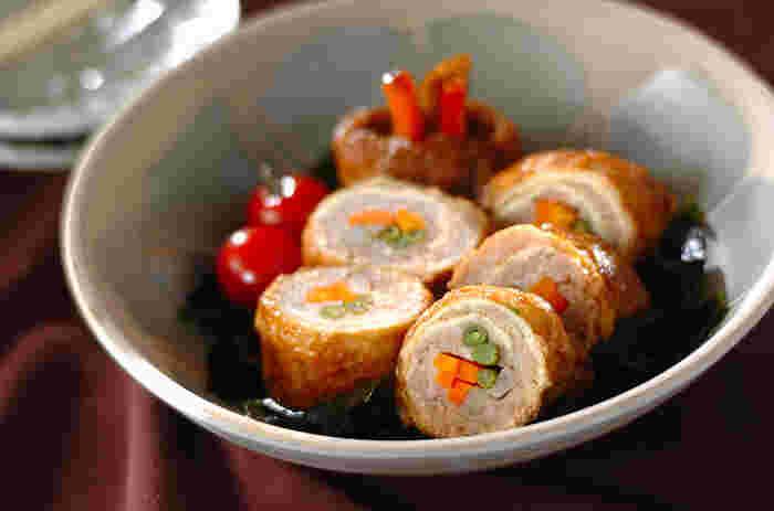 油揚げで鶏ひき肉を巻いてボリューム満点に仕上げたロール煮。茶色く地味になりがちな煮込み料理も、人参やインゲンなど彩り野菜を一緒に巻くことで、見た目にも美しい一品になります。