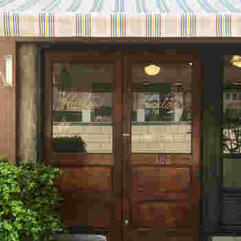 やわらかいピンクベースのストライプのテントが目印。 ハンサムな扉に、女性らしい流れるようなロゴサインというバランスが絶妙!