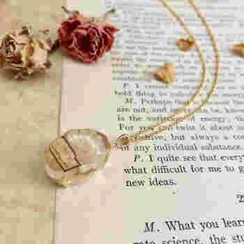 宝石のようなオーバルカット型が美しい、ドライフラワーのネックレス。生成り色のお花とラベルを閉じ込めて標本にし、クラシカルな印象になっています。