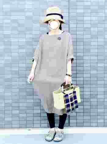 ワンピースとサンダルはグレーで合わせて、帽子とかごバッグの色も同じでまとめたコーデに、ネイビーが差し色になっています。単色のワンピースには小物でポイントをつけましょう。