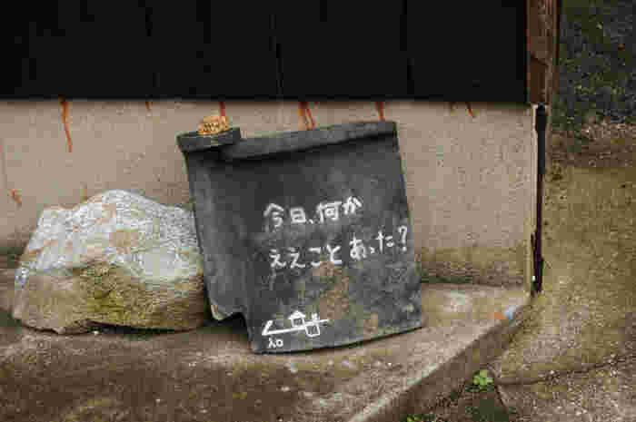 瓦に書かれた「今日、何かええことあった?」の看板。くすっと笑えるアートに心が和みますね。