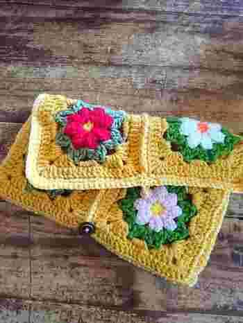 鮮やかなミモザ色の毛糸をメインに編みあげたクラッチバッグ。モチーフを6つをかがってボタンをつけるだけで完成です。肩紐をプラスしたらショルダーバッグとしても使えますね。