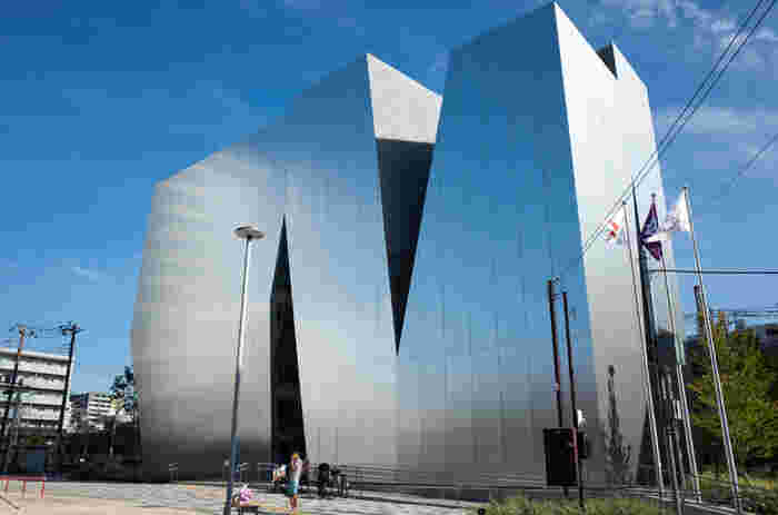 鋭角に切り取られたシャープなフォルムが印象的な、すみだ北斎美術館。ミラーの外観に青空が映ると、つい見惚れてしまう美しさ。建築界のノーベル賞とも呼ばれるプリツカー賞を受賞し、国内外で活躍する妹島和世氏(せじま かずよ)の建築です。