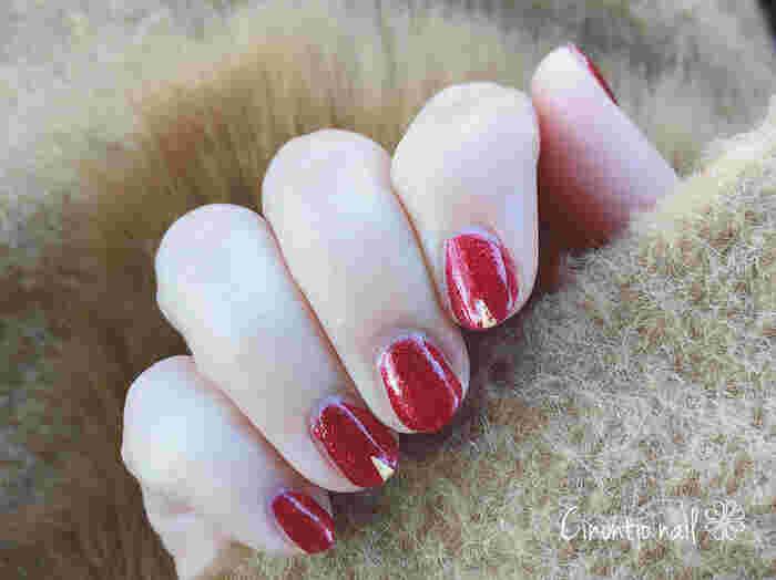ツヤツヤのりんごのような「赤」が素敵なネイル。人差し指と薬指にあしらわれたスパークルスタッズで、パーティにもぴったりな華やな印象に。