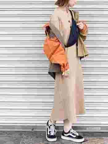 ラテカラーのワンピースを着たら、あわせる小物の色も楽しみたいポイントです。ブルゾンのオレンジの差し色が、ラテカラーコーデを活動的な印象にしてくれています。同系色のポイントカラー使いで、まとまりがありながらもアクセントになる着こなしです。