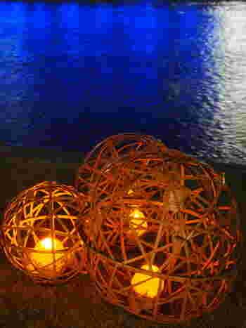 竹飾りから漏れる光が柔らかに訪れた人たちの足元を照らしてくれます。ライトアップされた周辺の明かりを映した川面との対比が楽しめますね。