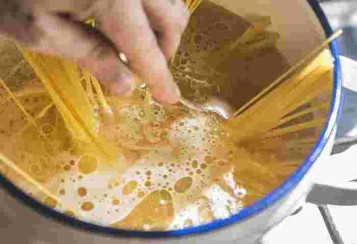茹で始めたら、たまに箸で大きく混ぜる程度にし、かき混ぜすぎないことがポイントです。パスタの袋に記載されている茹で時間より1分程度短く茹でると理想的なアルデンテになりますよ。茹で時間が近づいたら一本手に取ってみて断面に細く芯が残っていればOKです。
