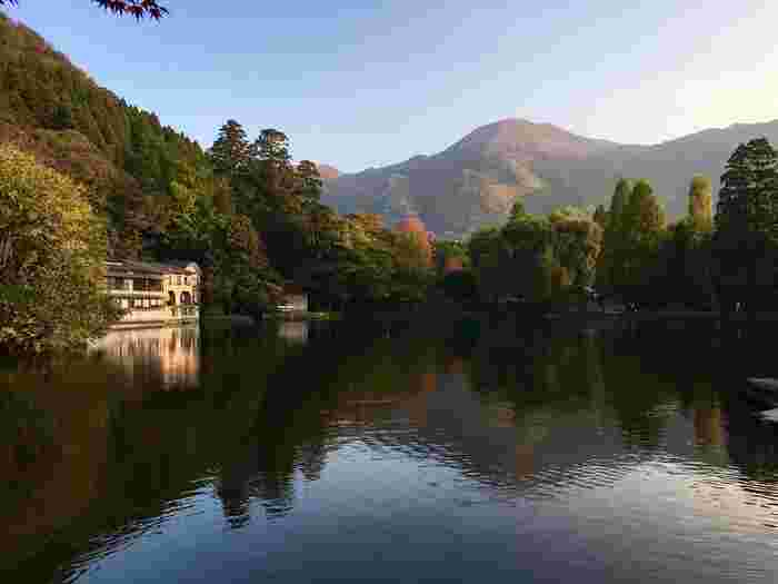湯布院を代表する観光地、「金鱗湖(きんりんこ)」。実は不思議なことに、湖底からは温泉が湧く湖なのです。寒い日の朝には湖面から湯気が立ち上る、幻想的な朝霧を愉しむこともできますよ。  さらに秋は、このように紅葉が綺麗です。