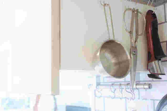 レンジフードの溝にフックをひっかけて、キッチンでよく使うものを吊り下げ収納。キッチンの奥まで入らないと見えない死角を利用した収納方法です。