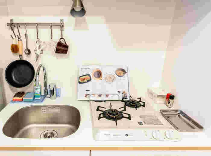 清潔感のある真っ白なかわいらしいキッチン。シンプルで素敵ですが、作業スペースや物を置くスペースがほとんどありません。 使用頻度の高いキッチンツールはポールに吊るして収納。 スポンジなど水切れが気になる小物は、金網とカウンタークロスを上手に組み合わされています。