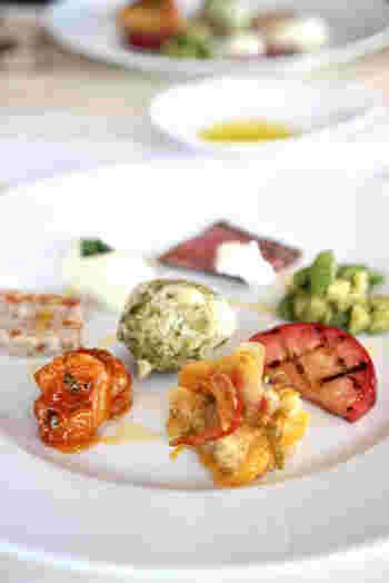 イタリアンの巨匠、片岡シェフがプロデュースしたレストランということもあり、本格的なメニューがいただけると評判です。ランチはコースの1種類のみで、こちらは前菜の盛り合わせ。彩り豊かで、白いプレートにアートが描かれたよう。