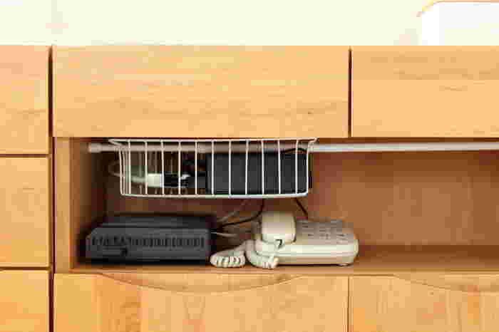 ワイヤーラックに突っ張り棒を通して、リビングキャビネットに設置。ルータやケーブルなどのごちゃごちゃする配線関連のものをまとめて、浮かすように収納しています。配線まわりがスッキリすると、見た目もきれいで掃除もラク。うれしいですね。