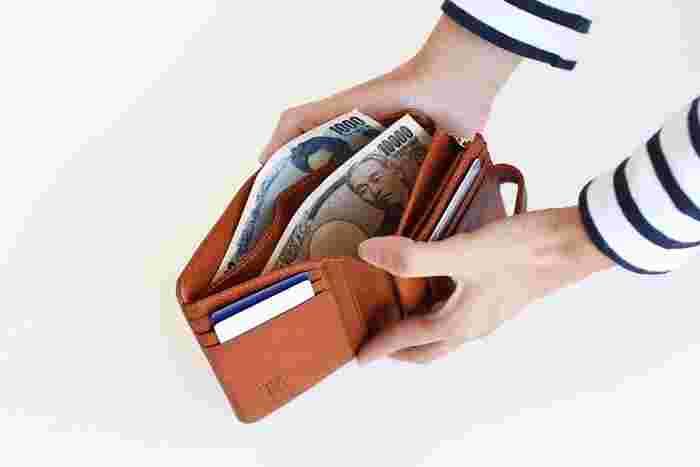 二つ折り財布は、その名の通り、二つ折るタイプなので、長財布に比べてやや半分の横幅。その分厚みが増しますが、片手で持つのに馴染みやすいサイズ感が魅力です。このようにボタンで閉めるタイプのほか、サイドの隙間を埋めてくれるラウンドファスナータイプも主流です。  長財布に比べて、容量は少なめですが、片手で気軽に持ち運べて、ぱっと小銭を取り出しやすいのがポイント。