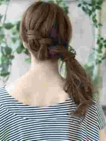 後ろの髪をざっくり2つに分けて、片方を編み込みにしてからもう片方の髪と一緒にゴムで結びます。 ゴムの結び目にふわっと髪を結びつけると、より素敵に仕上がりますよ。