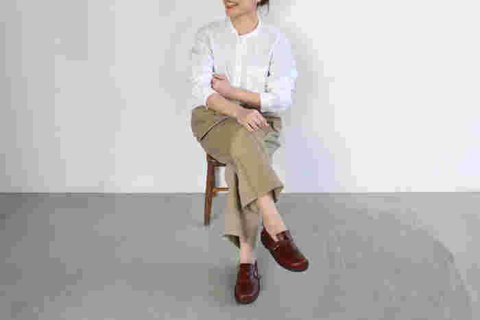 """こちらは白シャツ×チノパンのシンプルな装いに、スリップオンタイプのシューズ「PISAC(ピサック)」を合わせた大人のカジュアルスタイルです。PISACの""""Rumba(ルンバ)""""は、深みのある落ち着いた""""赤""""が印象的。足元を女性らしく華やかな雰囲気に演出してくれます。"""