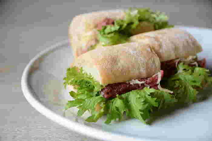 """メニューでは、さまざまな種類のサンドイッチが食べられます。「六角堂ルーベンサンド」は、ニューヨークで定番のルーベンサンドをもとに、""""チャバタ""""というパンにコンビーフやザワークラウトなどを挟んで六角堂風にアレンジしたもの。サンドイッチやドリンクなどはテイクアウトもできますよ。"""