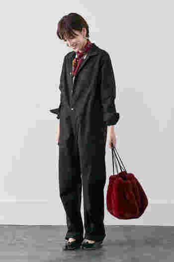 メンズライクな黒のジャンプスーツを、スカーフやパンプスでレディライクな印象に仕上げたコーディネートです。ボリューム感のある赤のファーバッグが、女性らしさをグッと高めてくれます。