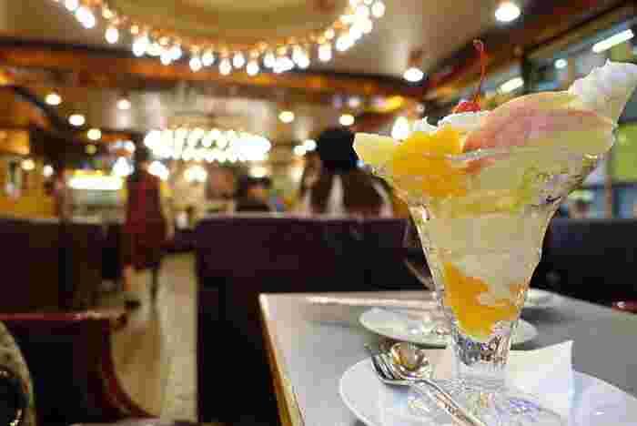 上野駅近くにある「ギャラン」は、昭和52(1977)年にオープンした喫茶店です。 開店当時の雰囲気を今に伝える店内は、シャンデリアが下がり、綺羅びやか。座席は、ゆったりとしたソファ席。昭和からの営業していても、清潔感があり、居心地も良いと評判です。【明るい店内と人気メニュー『フルーツパフェ』】