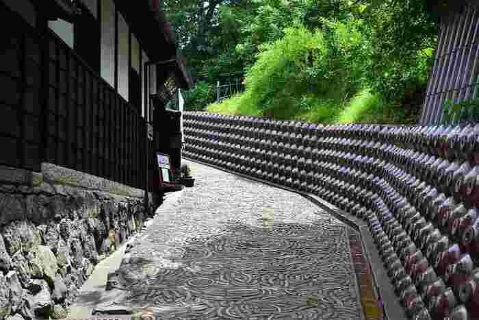 焼酎瓶で埋められた壁が続く独特の景観を持つ小路は、「デンデン坂」と呼ばれています。