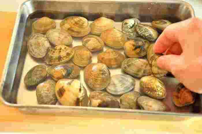 あさりを調理する前には砂抜きを行うようにしましょう。海水と同程度の塩水をバットに作り、あさりは重ならないように入れておきます。砂抜きが終わったら、ざるに入れて殻と殻をこすり合わせるようによく洗います。