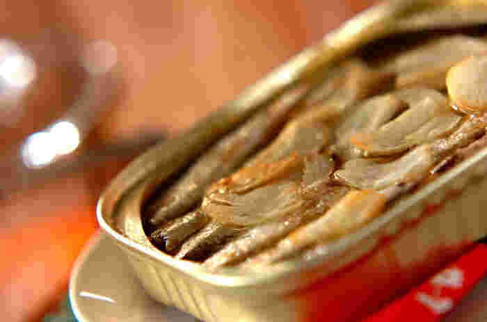 「イワシのアヒージョ」は、オイルサーディンの缶詰にニンニクのスライスを載せてオーブントースターで加熱するだけ、という超簡単レシピ。  アヒージョにはキノコを載せてもおいしいです。
