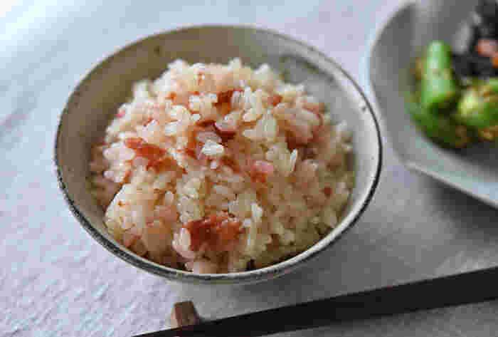 梅の炊き込みご飯は、梅干しを潰す手間がなくとても簡単。丸ごとの梅干しを一緒に炊き込みます。  コツは、いったんお米を浸水させて引き上げること、調味しただし汁で炊くこと。梅干しだけで炊くより、しっかりと味が付いて、美味しくいただけます。炊き上がりにご飯を混ぜると、梅干しが自然に潰れて、ご飯全体が色づいて華やぎますよ。