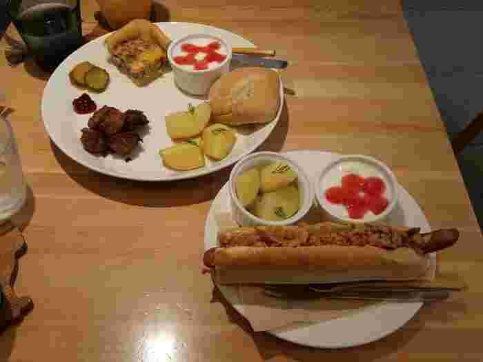 北欧の家庭料理のプレートとフライドオニオンがたっぷりのったホットドッグ。かもめ食堂を思わせる雰囲気の中で食べる家庭料理にほっこり癒されてしまいそうですね。