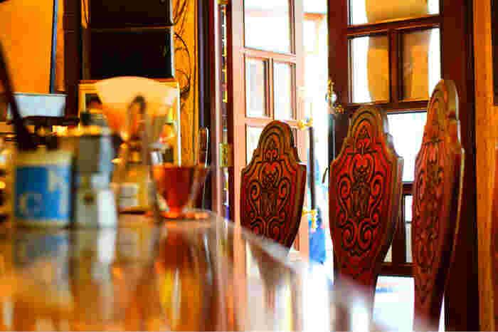 """木彫りの細工が施された椅子には和蘭豆(らんず)の""""R""""の文字が。食器棚やランプなど、年月を重ねた道具のひとつひとつが見る価値あり。"""