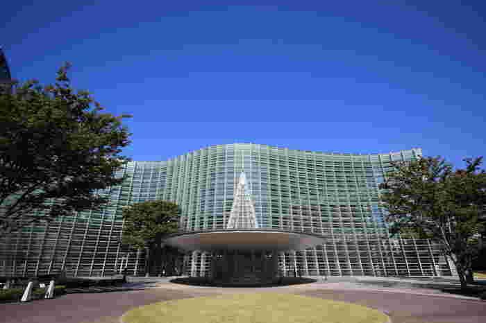 丸みを帯びたうねりが印象的な外観の国立新美術館は建築家・黒川紀章氏が手がけたもの。