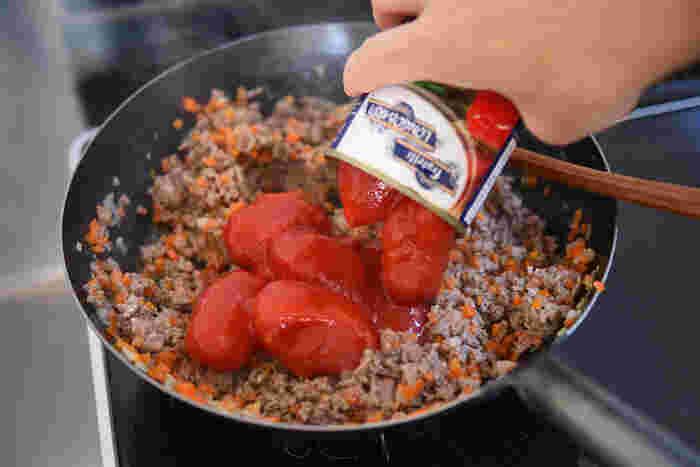 トマト缶はホールのものを使い、お好みの大きさにヘラでつぶして。空いたトマト缶に水を入れて、缶に残ったトマトもきれいに使いきりましょう。