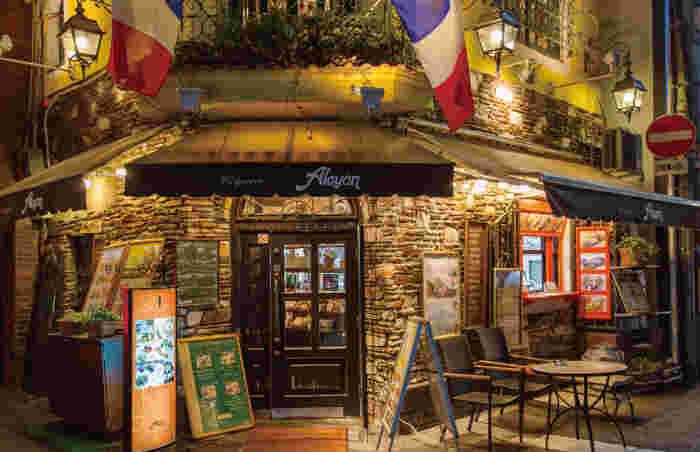 クレープリー・アルションは、「大阪ミナミ」の愛称で親しまれている難波と心斎橋をつなぐ戎橋筋商店街から一歩足を踏み入れた場所にあるクレープ専門のカフェレストランです。石造りの壁でできた建物は、ヨーロッパの民家のようなかわいらしさです。