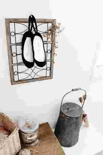 くすんだ色のフレームに、黒の靴下を吊るして、まるでバレエシューズを吊るしているようなインテリアに。さりげなく飾ったドライフラワーもアクセントになっています。