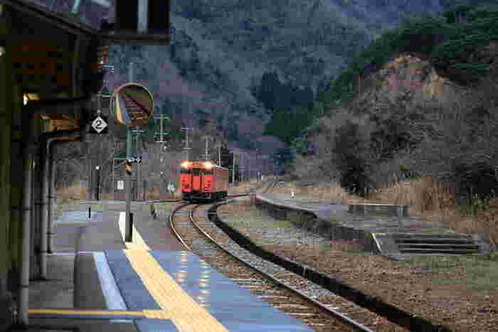 兵庫県と鳥取県の県境近い場所に位置する居組駅は、山陰本線沿線にある1911年に開業された無人駅です。100年以上もの歴史を誇る居組駅は、人里離れた山奥にひっそりと佇んでおり、ノスタルジックな雰囲気を醸し出しています。