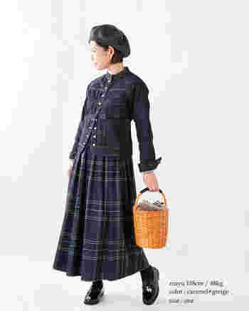 ファーつきのかごバッグで、定番のトラッドルックにはずしを加えて。淡くナチュラルな色合いが、ダークカラーのコーディネートに明るさを呼び込みます。