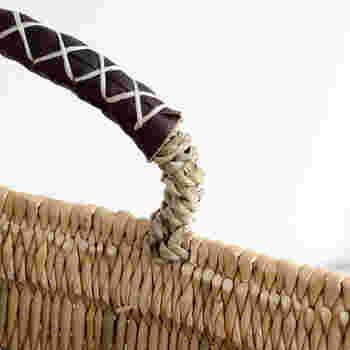 取っ手部分はしっかりと本体に編み込まれ、丈夫に作られています。持ち手の革に縫われたクロスもかわいらしい表情を添えていますね。