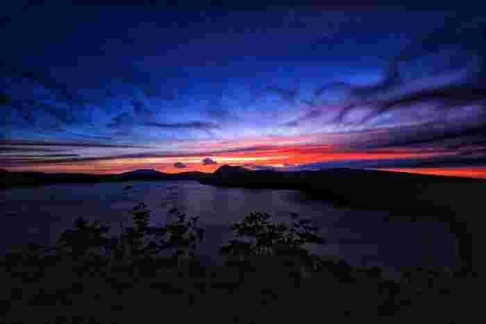 四季折々、時間帯によって様々な表情を見せてくれる摩周湖ですが、摩周湖で臨む夜明けの美しさは格別です。静かな湖面、朝陽の光を反射して紅に輝く雲、夜空の残光のような藍色の空が織りなす景色は、まさに絶景そのものです。