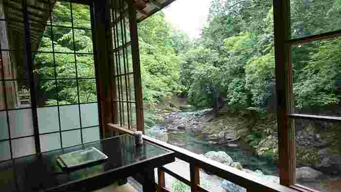 「瓦そば 松右衛門」は、周山街道から渓谷へと降りる小径の先。 ガラス戸と柱の店内は、涼やかで開放的。テーブルは全て清滝川側に並べられ、どの席からも清流の素晴らしい景色が楽しめます。
