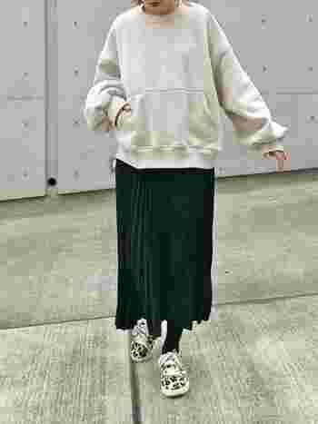 フェミニンなスタイルが苦手な人は、モノトーンでまとめるのが正解。スウェットに黒のプリーツスカートを合わせましょう。アクセントには、目を引くヒョウ柄スニーカーでらしさをプラスして。