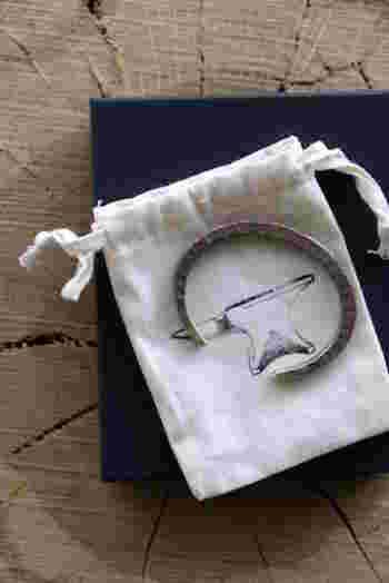 角形のデザインがおしゃれな「BRADDOCK CUFF」は、女性の腕に上品に馴染むスマートなフォルムが魅力的です。バングルには専用ボックスと可愛い巾着袋が付属しているので、大切な方への贈り物にもぜひおすすめですよ。