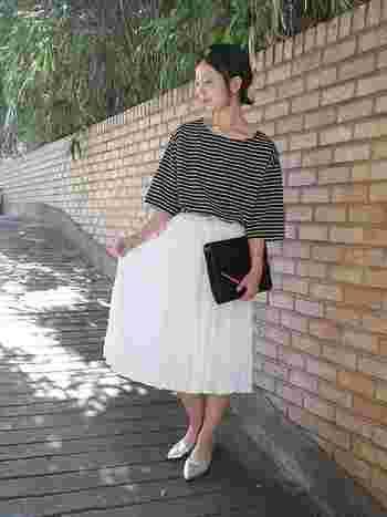 モノトーンコーデは、白のスカートを合わせると明るめに仕上がります。クラッチバッグやパンプスできちんと感をアップ。