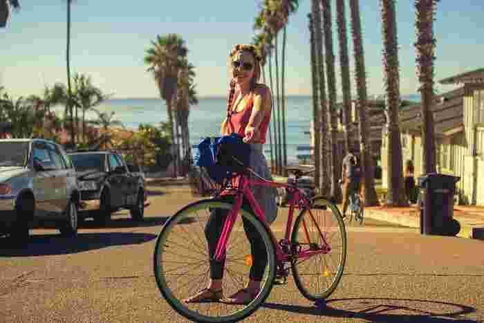 笑顔がまぶしい南国スタイル。ピンクの自転車も街に似合っています。