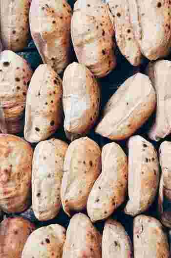 """ピタパンの""""ピタ""""はヘブライ語で、""""アラブのパン""""という意味です。パンそのものの歴史は、紀元前4000年頃の古代メソポタミア~エジプトで生まれたとされ、当時は平たいパンがよく食べられていました。この平らなパンに発酵が加わることで生まれたのがピタパンです。中近東の人たちの間では、ひよこ豆をベースにしたペースト状の""""フムス""""や野菜、シシカバブなどの肉、""""ファラフェル""""と呼ばれるひよこ豆のコロッケ、などを挟んで食べるのがメジャーなのだそう。"""
