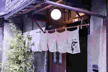 「谷中ビアホール」は、昭和13年に建てられた住宅をリノベーションした複合施設「上野桜木あたり」の1号棟にあります。3軒続きの古民家の1軒で、のれんや丸い電球などレトロで趣きのある外観が印象的です。
