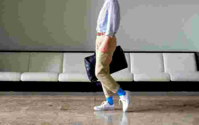 明るい水色の靴下がストライプのブラウスや白いスニーカーとあいまって爽やかな印象。ロールアップして適度に色を楽しみたい。