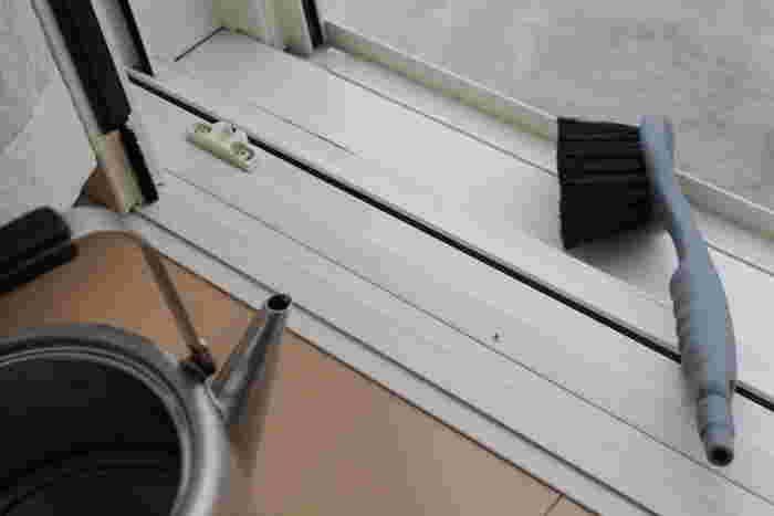 サッシの溝は、やかんの水を掛けながらブラシで磨くと効率よくきれいになります。大小のブラシを使い分けながら汚れをかき出し、最後にマイクロファイバークロスで拭き取ります。