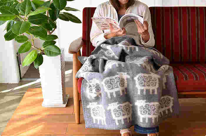 ブランケットは夜にソファでくつろぐときにひざ掛けとして使ったり、寝るときにちょっとした毛布代わりとしても使えます。ラムウールを使用しているため、ふんわりとやわらかな肌触り。くるくるとした羊にほっこりとするデザインで、リバーシブルになっています。